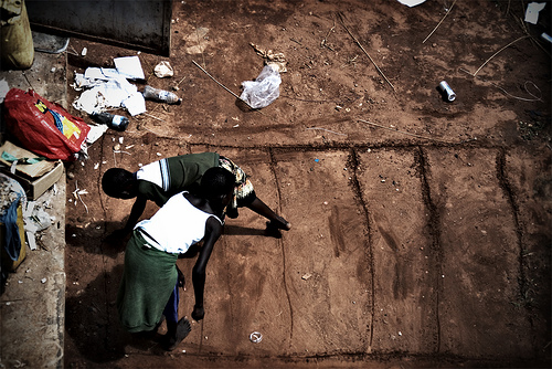 Ugandan girls play hopscotch in the dirt