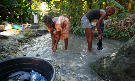 Women washing clothes in small creek