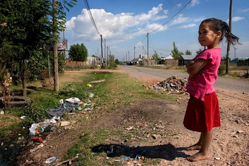 Young girl in Buenos Aires, Argentina collects trash with family.