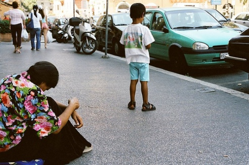 Roma woman and child panhandle on streets of Rome, Italy