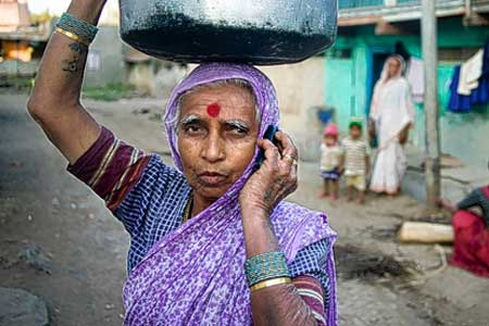 Indian woman listens to handset while working