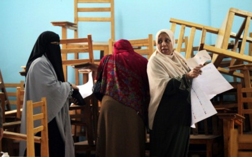 Islamic women organize their ballots amongst a cluster of chairs