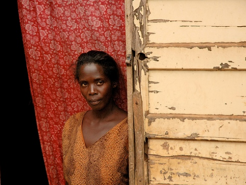 Ugandan woman stands in doorway