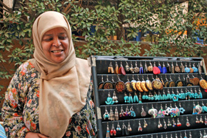 Woman displays handcrafted earrings that she sells