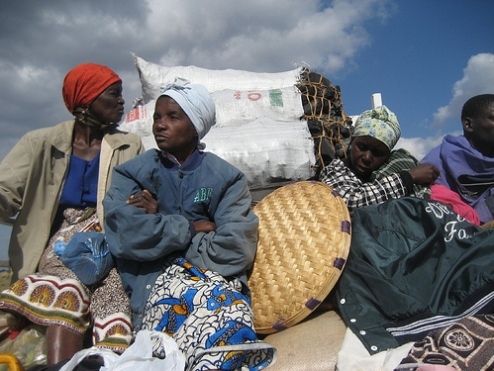 Women ride wagon with charcoal delivery in Mozabique