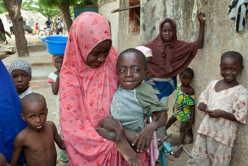 Nigerian sister holds sibling who is a polio victim as mother looks on with other children