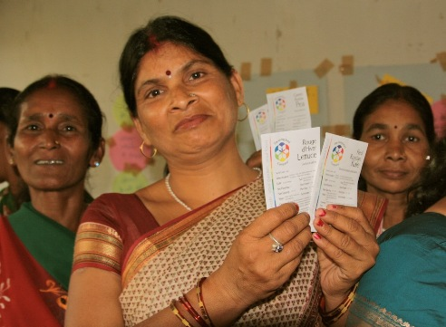Women farmers from India hold up heirloom food crop seeds