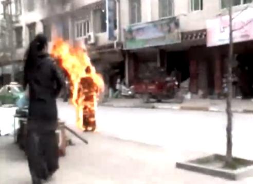 Tibetan Bhuddhist nun stands in street after setting herself on fire