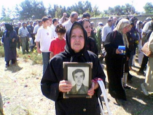 Iranian mother holds picture of disappeared son