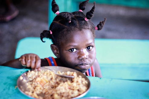 Girl in orphanage in Port-au-Prince eats rice