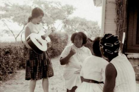 Fannie Lou Hamer talking young girls and women outside her home in 1964