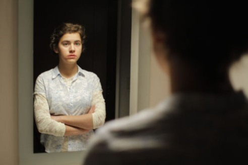 Main character in film 'After Lucia', Alejandra, looks in mirror at injuries