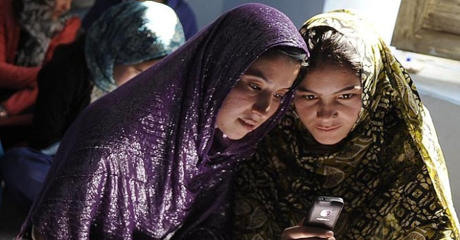 Women students looking at the screen of a cellphone