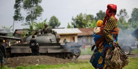 Woman and child looking at a tank and soilders
