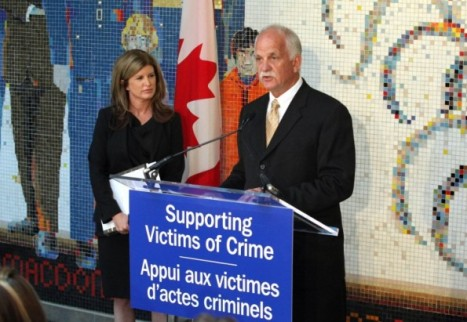 Rona Ambrose and Vic Toews standing at a podium with banner reading 'Supporting Victims of Crime'
