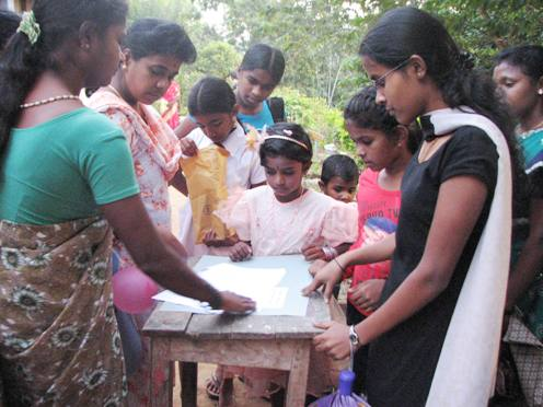 Children in Sri Lanka stand around a petition table for domestic worker Rizana Nafeek