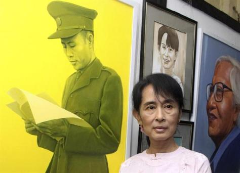 Aung San Suu Kyi poses by a painting of her father, Gen. Aung San