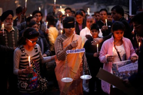 An Indian girl dressed as Lady Justice takes part in a candlelight vigil