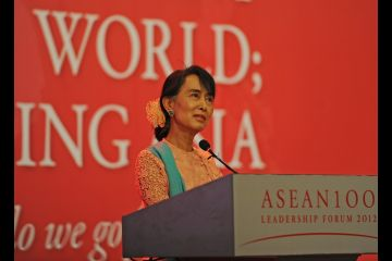 Aung San Suu Kyi speaking at a podium.