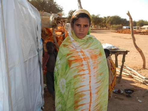 Girl waits for Mali family in a displacement camp in Burkina Faso