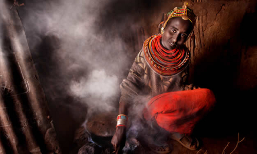 A woman in the Horn of Africa cooks in a smoke-filled room