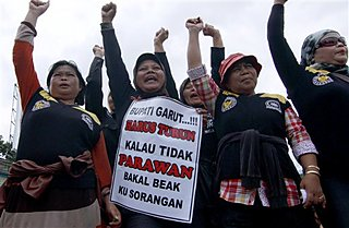 Indonesian Women shout slogans, wave signs, and wave 'power' fists