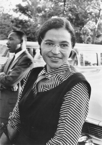 Rosa Parks sitting on a park bench with Rev.Martin Luther King Jr. in the back ground
