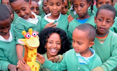 Ethiopian Television Producer Buktawit Tegabu surrounded by kids who are excited to touch on of the characters in her TV series 'Tsehai Loves Learning.'
