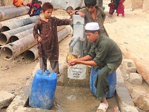 Children in the Helmad Refugee Camp in Kabul, Afghanistan pump water