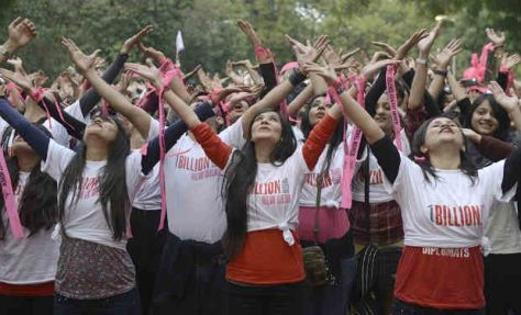 Many women with their arms in the air and wearing One Billion Rising T-shirts
