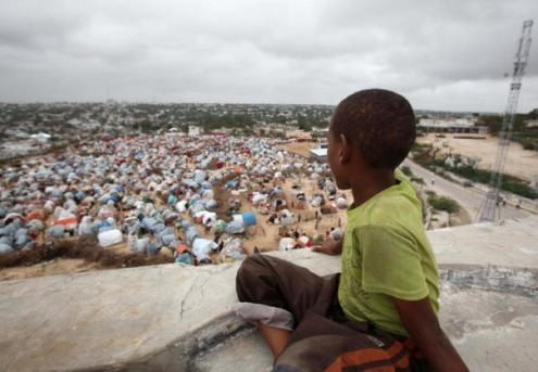 Somali displaced boy looks out on settlement camp