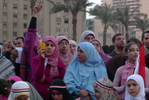 Young woman holds up mobile phone as she takes pictures during protests in Cairo, Egypt