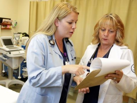 Nurse practitioners Michele Knappe, left, and Julie Zimmer go over a patient's chart