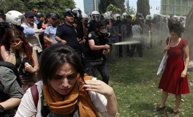 Masked policeman teargas women wearing red