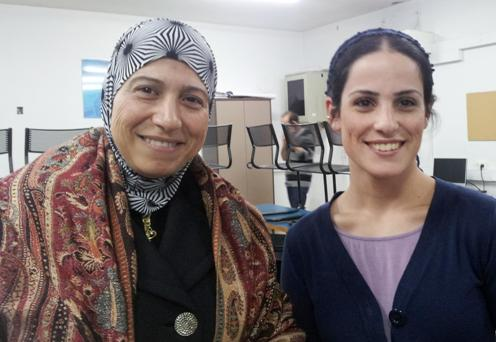 An Arab-Israeli and Jewish-Israeli teacher stand together during a teacher training session