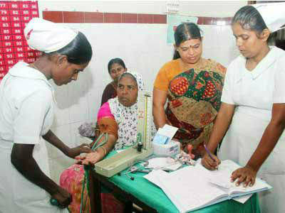 Female nursing students gather around patient