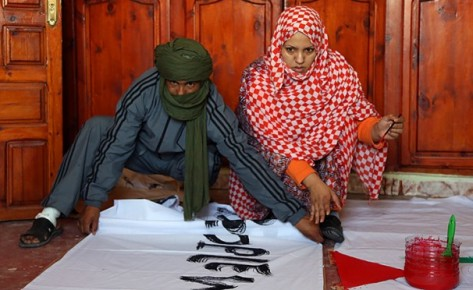 Western Sahara Woman and Man work on banner