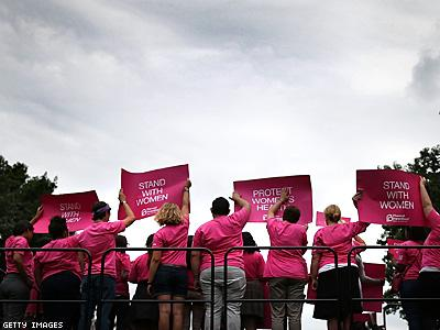 Women and men stand together in Stand with Women rally