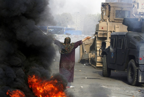 Cairo womena protester stands before a military bulldozer