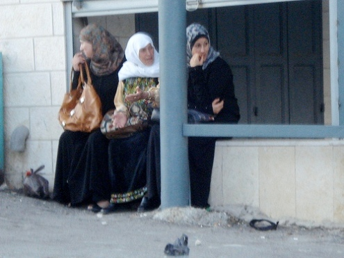 Three women sit at the Israeli checkpoint at between Bethlehem and Jerusalem