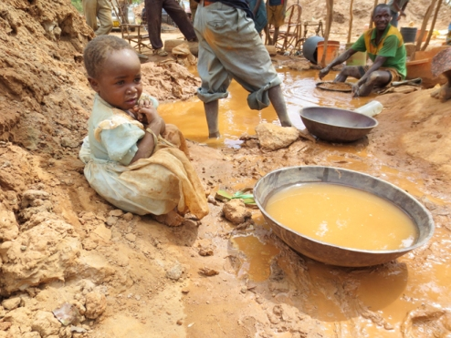 Tanzanian child plays in mercury laden water as adults process gold