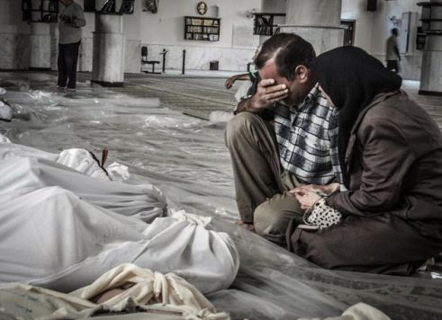 Parents identify a dead child after chemical attack in Damascus, Syria