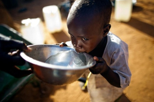 Boy drinking water in a North Darfur IDP camp, Africa
