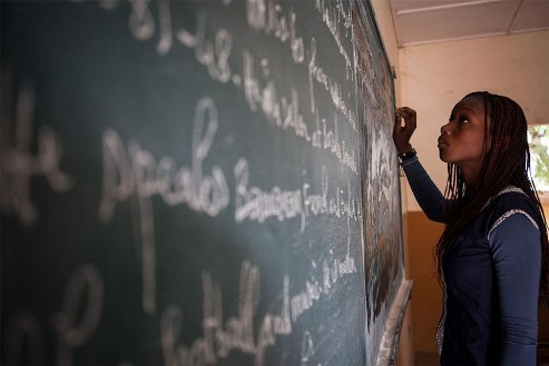 Mali schoolgirl writes on blackboard