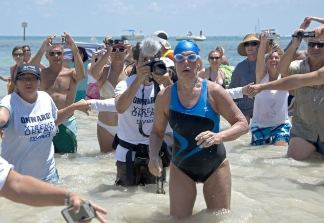 Diana Nyad coming out of the ocean surrounded by reporters