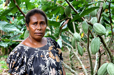 Papuan woman standing by her crops