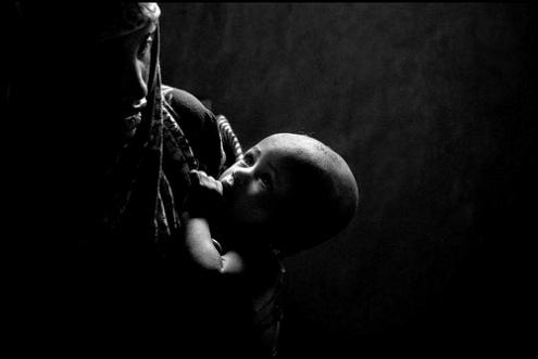 Refugee mother feeds her child