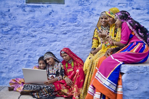 Women share laptop and cell phone