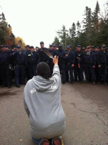 This photo of 28-year-old Amanda Polchies kneeling before Royal Canadian Mounted Police while brandishing an eagle feather during anti-fracking protests in New Brunswick has become iconic as a symbol of resistance to destructive industrial development---and of women's role in fighting for water. Image: Ossie Michelin, APTN Natonal News