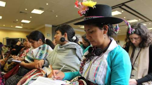 Women with headphones and note pads sit at a conference.